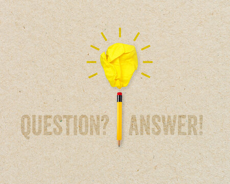 Paper light bulb and pencil with faq question and answer - frage und antwort on brown recycled paper background