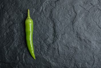 A single hot chili peppers on black background