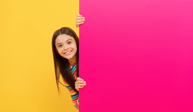 happy teenager girl behind pink paper sheet with empty place for copy space, advertising