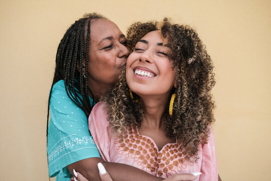 African mother kissing and hugging her adult daughter outdoor - Family, mother and adult child love