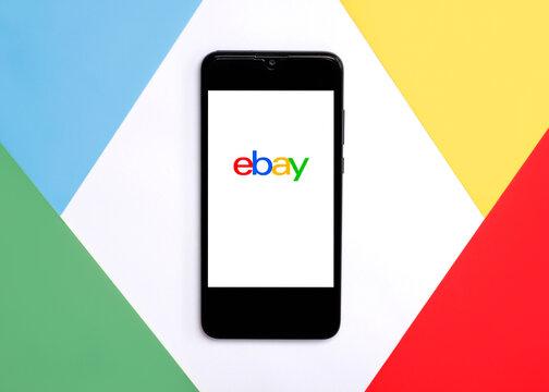 Ebay logo on white screen of smartphone on colorful background.Ebay app