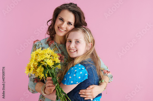 smiling trendy mother and child hugging on pink