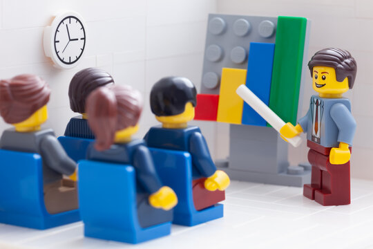 Tambov, Russian Federation - February 26, 2021 Lego businesspeople minifigures having a meeting and discussing graphs showing the results of their successful teamwork.