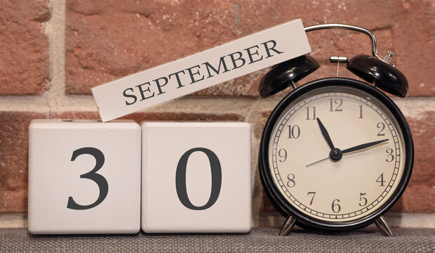 Important date, September 30, autumn season. Calendar made of wood on a background of a brick wall. Retro alarm clock as a time management concept.