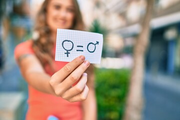 Fototapeta Young blonde girl smiling happy holding paper with gender equality concept walking at the city.