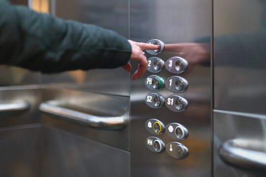 woman pressing a button on an elevator to go to a floor
