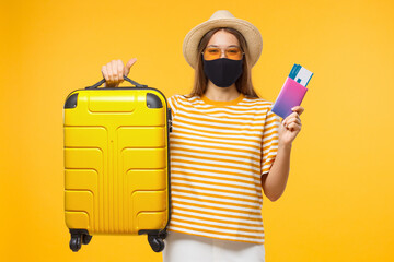 Obraz Immunity passport. Happy young woman tourist is ready to travel, holding suitcase and tickets to safe flight after end of coronavirus lockdown or having negative covid test - fototapety do salonu