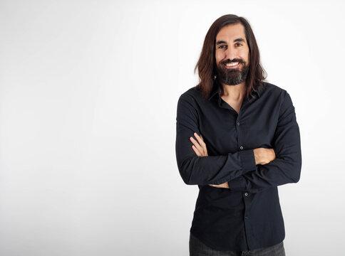 hombre sonriente sobre fondo blanco blusa negra con los brazos cruzados