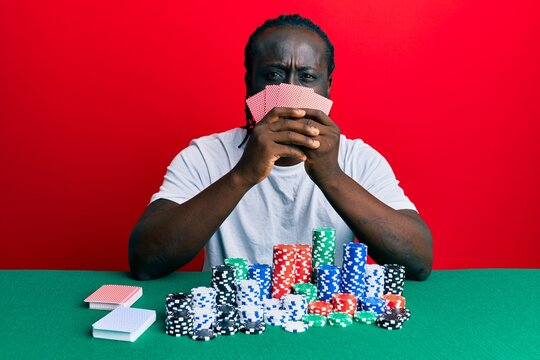 Handsome young black man playing gambling poker covering face with cards skeptic and nervous, frowning upset because of problem. negative person.