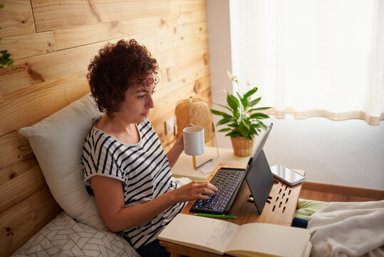 Woman telecommuting from her bed while holding a cup of coffee.