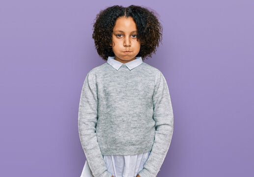 Young little girl with afro hair wearing casual clothes puffing cheeks with funny face. mouth inflated with air, crazy expression.
