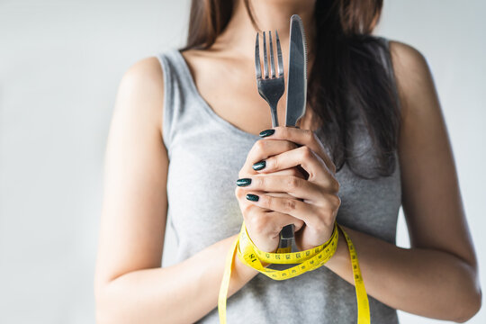 diet for good health concept. Woman tied her hand and restraint do not to so much food.