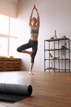 Young woman doing yoga Tree pose, Vrikshasana