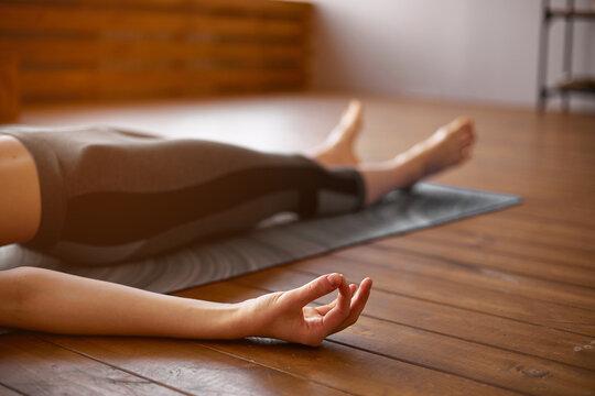 Young attractive woman practicing yoga, Savasana pose