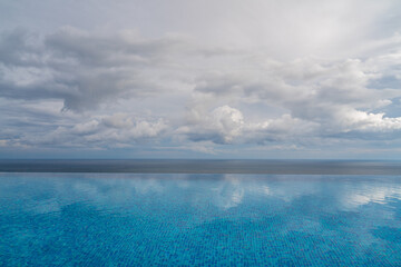 Infinity pool with sea and ocean views on the background of the sky with clouds. The clouds are reflected in the pool.