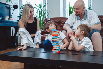 Two youth boys construct a tower from bricks competing each other and with their parents at home. Wall mural