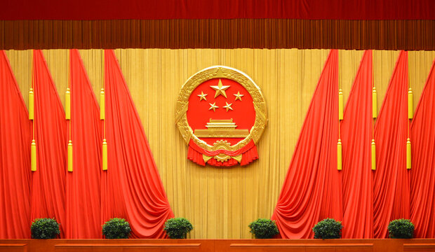 National emblem of the People's Republic of China and Red flags at the Great Hall of the People in Beijing, China on March 13, 2014