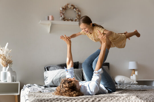Mommy helps me fly. Energetic young mom lie on bed play with active little daughter lift child in air on outstretched legs. Excited small girl flying raised up by grown elder sister enjoy funny yoga