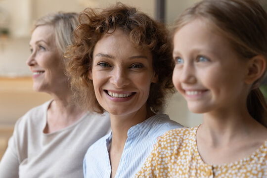 Generational similarity. Three generation family females relatives of diverse age old grandma adult mom daughter kid sit in row together. Focus on smiling face of young woman at centre look at camera