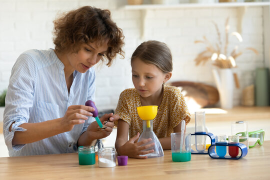 Little scientist. Curious school age daughter play with mom engaged at education activity make funny experiment. Interested small girl watch elder sister doing chemical test use chemistry set for kids