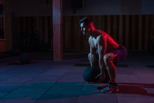 A muscular powerful man with a naked torso exercises with a heavy bag in a red blue neon light. Cross workout in a modern gym
