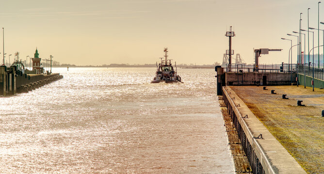 Tugboat leaves the harbor basin in the late afternoon and plunges into the open sea, backlight shot before sunset