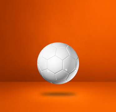 White soccer ball on a orange studio background