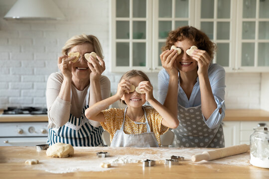 We love cooking. Cute multigenerational family older mature grandmother adult mother little daughter grandkid posing for funny portrait cook at kitchen look at camera make glasses from cookies hearts