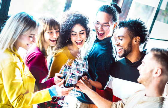 Young multiracial people drinking and toasting red wine at dinner party - Happy drunk friends having fun together at restaurant winery bar - Dinning lifestyle concept on bright vivid backlight filter