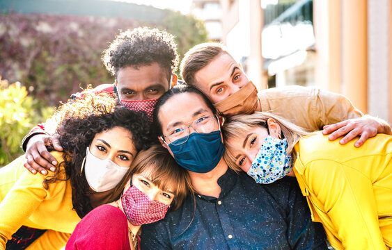 Multicultural milenial friends taking selfie smiling behind face masks - New normal friendship and life style concept with young people having fun together outside - Warm bright vivid filter