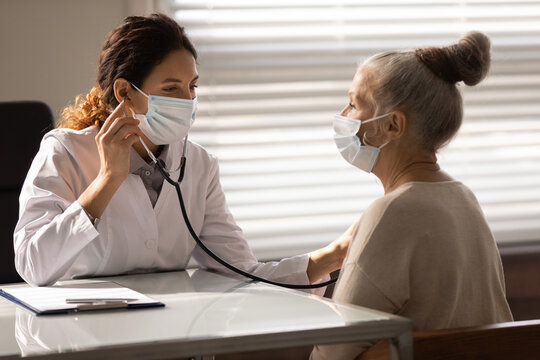 Close up female doctor wearing face mask checking mature patient lungs, holding using stethoscope, listening to elderly woman breath, sitting in hospital office, medical checkup and healthcare
