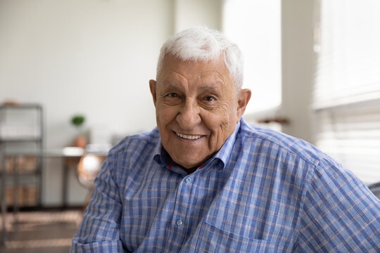 Head shot portrait smiling mature man looking at camera, happy grandfather chatting with relatives online, making video call, senior blogger shooting recording video, elderly teacher working online