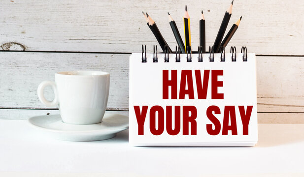 The words HAVE YOUR SAY is written in a white notepad near a white cup of coffee on a light background