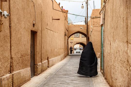 Iranian woman wearing black chador walking along street of Yazd