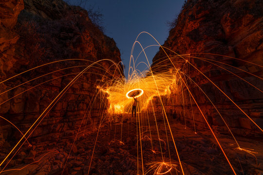Fire show, swirl, steel wool. Sparks from a metal in beautiful the canyon.