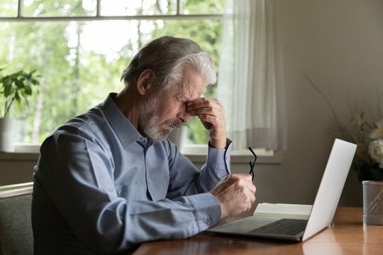 Tired mature 60s man working at laptop from home, taking off glasses, touching head and eyes. Old male pensioner suffering from headache, dizziness after looking at computer screen. Eye sight problem
