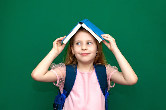 Child girl with a schoolbag and books in hands