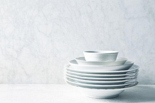 Stack of white porcelain plates and bowls on bright stone background. copy space