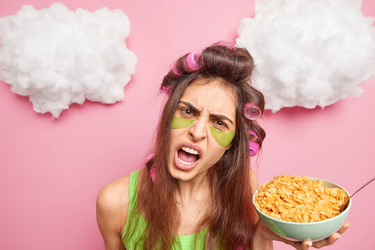 Headshot of angry displeased dark haired woman exclaims loudly keeps mouth opened reproaches you because of sleep interruption has breakfast holds bowl of cornflakes makes hairstyle with curlers
