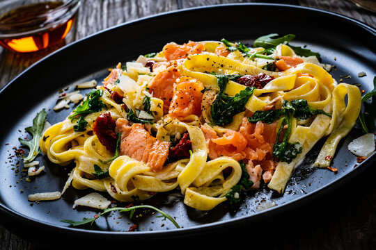Tagliatelle with salmon nuggets, arugula and sun-dried tomatoes on wooden table