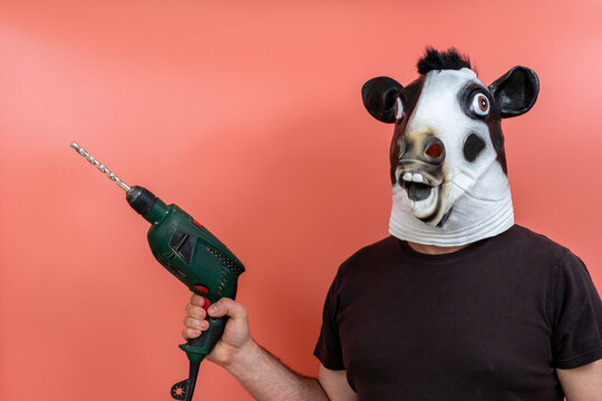 costumed person in cow mask using a drill