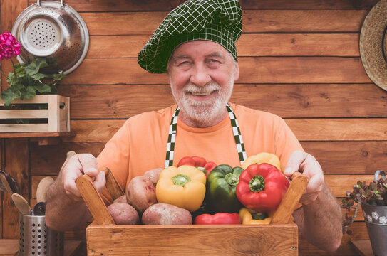 Happy and smiling senior farmer showing a wooden basket full of freshly picked peppers and potatoes from the garden
