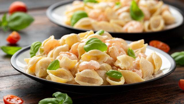 Italian conchiglie prawn, shrimp pasta in a creamy sauce on plate.