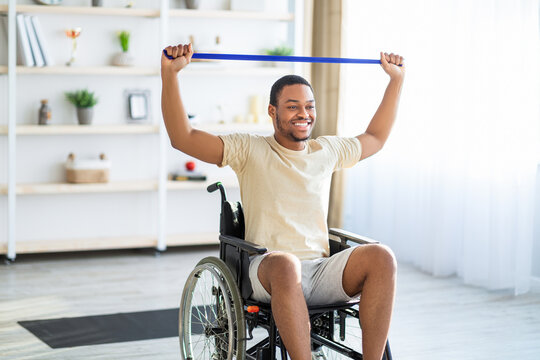 Happy black disabled man in wheelchair doing exercises with rubber band at home