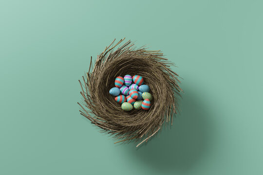 Colored easter eggs in a nest on a green background