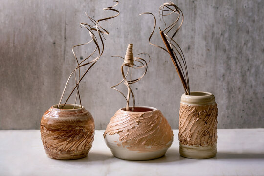 Three different shapes beige brown ceramic vases with dry flowers and twigs branch on white marble table with gray wall behind. Copy space.
