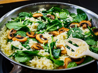 Risotto with champignons and spinach cooking in frying pan