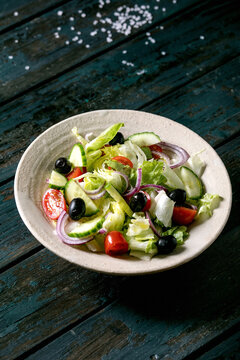 Classic vegetable salad with tomatoes, cucumber, onion, salad leaves and black olives in white ceramic plate. Dark wooden table.