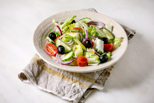 Classic vegetable salad with tomatoes, cucumber, onion, salad leaves and black olives in white ceramic plate on cloth napkin. White marble background.