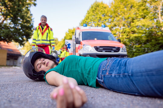 Motorcyclist laying on street with injuries after an accident